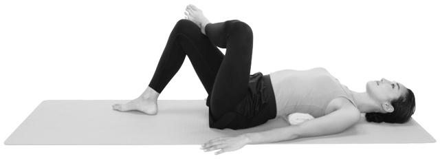 丸めたバスタオルを肩甲骨の下の位置に入れ、左右の腕を床につけた状態で仰向けになる