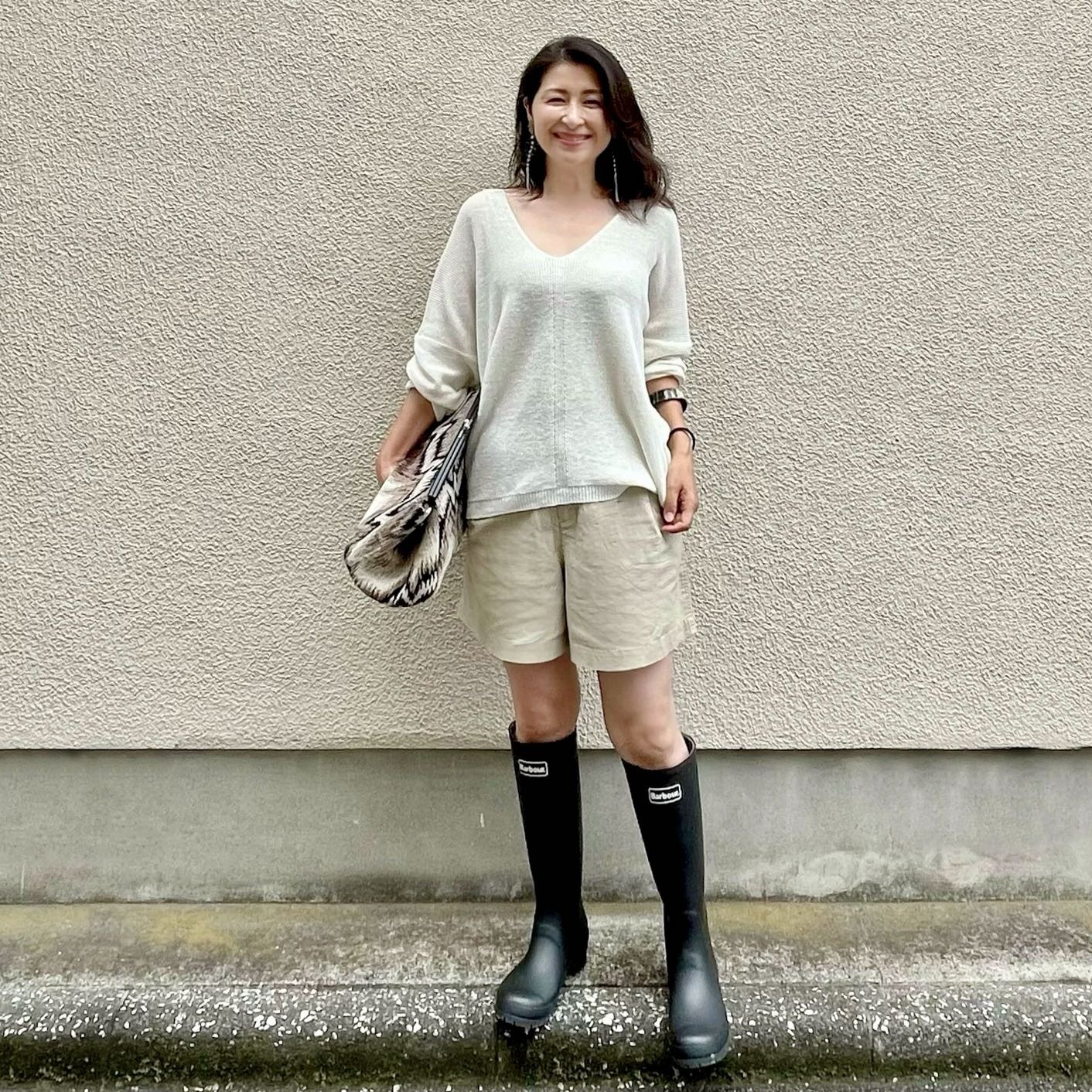 白のサマーニット、ベージュのショートパンツ、黒のロングレインブーツ、大きめクラッチバッグ