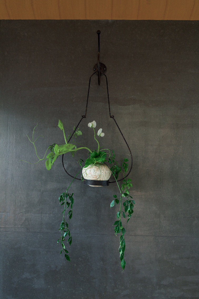 壁に吊るした小さな花器には