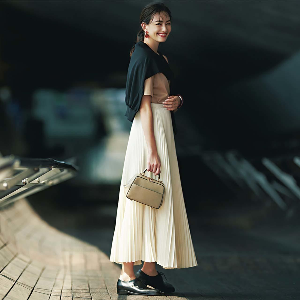 ベージュTシャツ×白プリーツスカート×黒カーディガンコーデを着たモデルのRINAさん