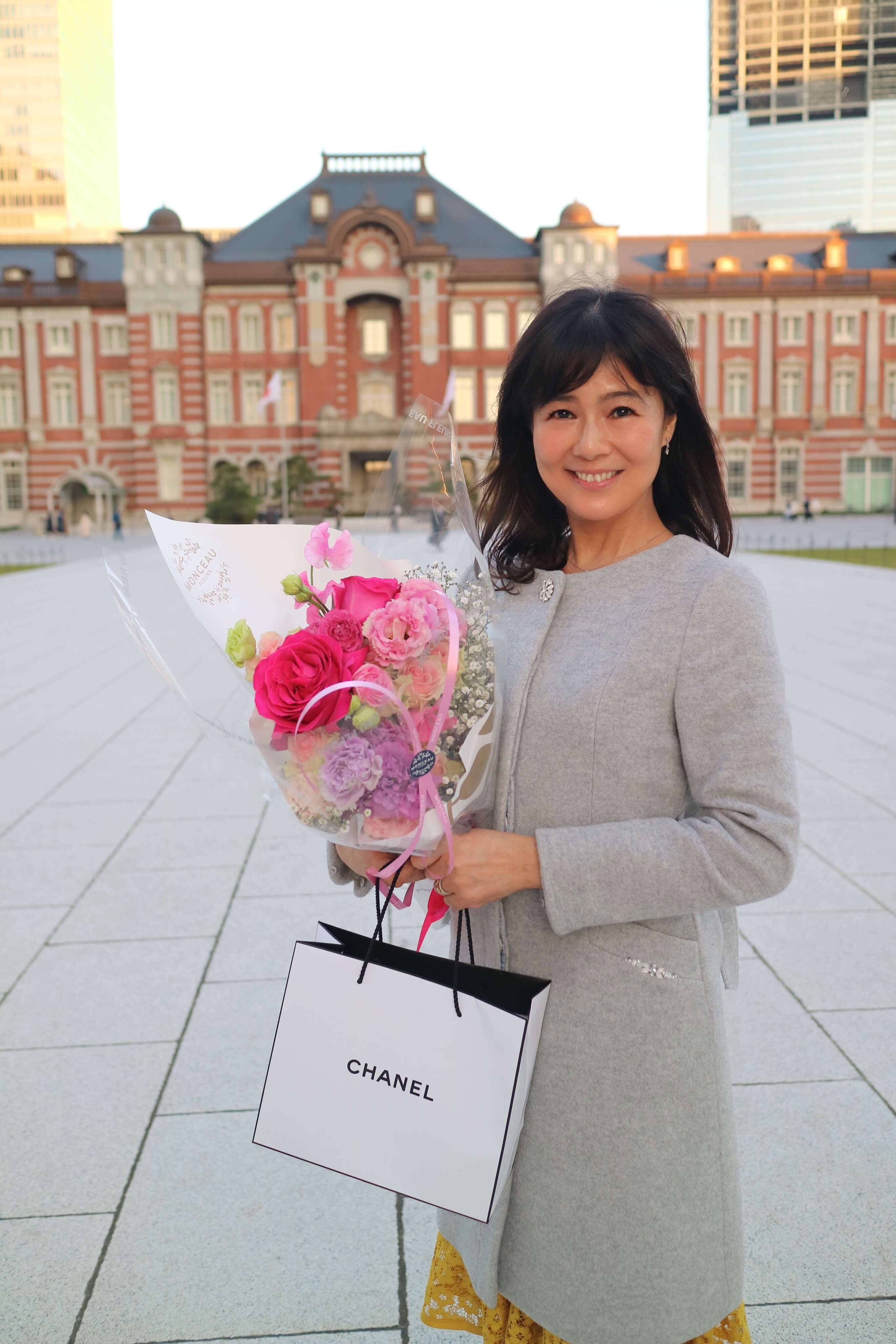グレーのコートでお誕生日の花束とプレゼントを持って東京駅の前で記念撮影