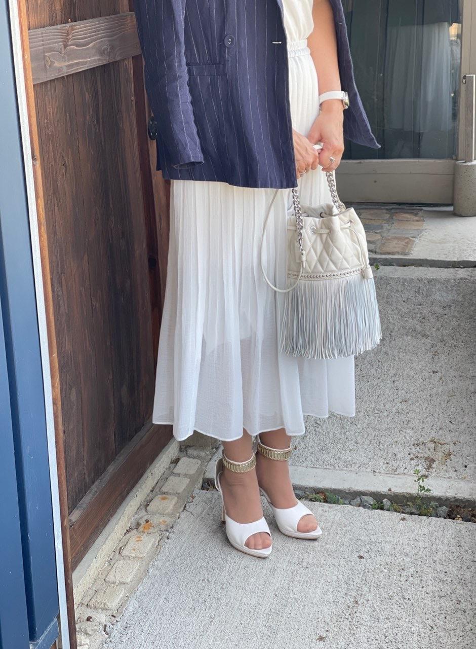 白いロングスカート、白いパンプス、白いバッグ