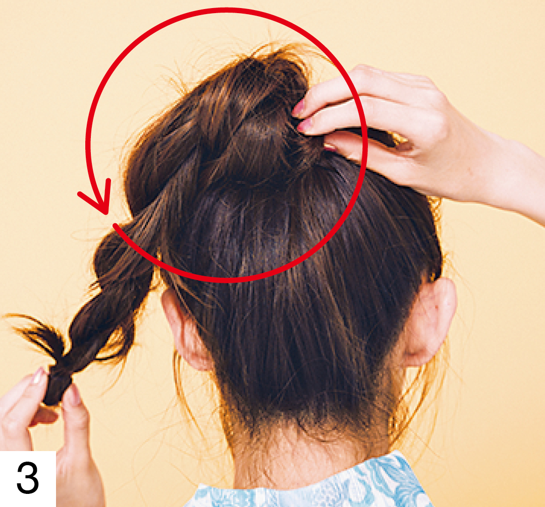 2本のねじり編みを作ったら、片方の毛束をもう片方の毛束の根元に巻きつけピンで固定、おだんごにする。もう1本もおだんごの回りに巻きつけて固定。