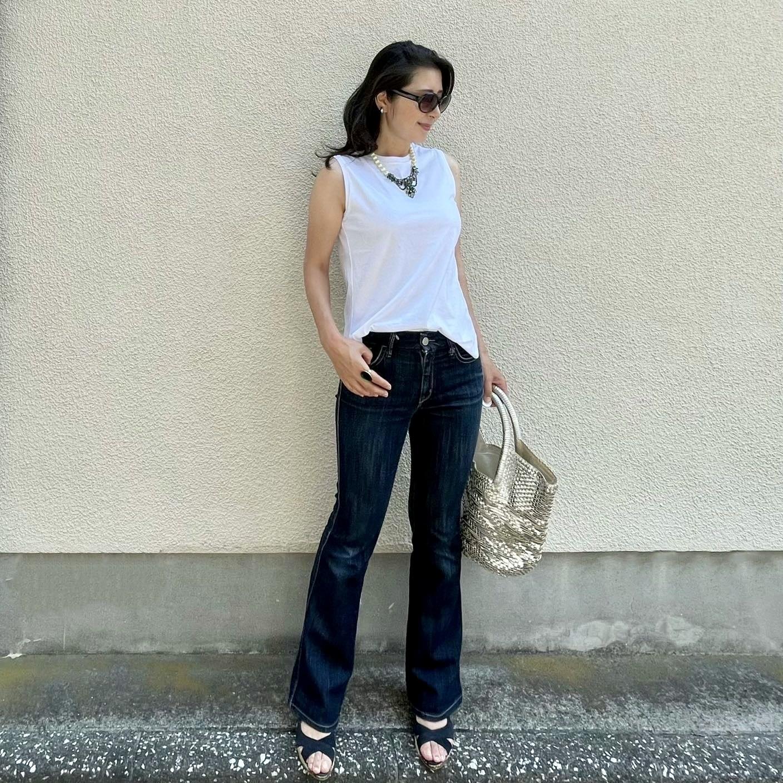 ユニクロの白ノースリーブTシャツ、ノンウォッシュのブーツカットデニム、シルバーの大きめバッグ、ネイビーのサンダル、パールとビジューのショートネックレス