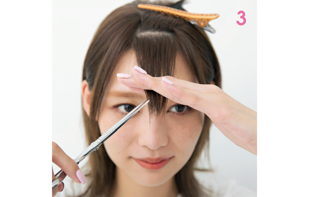 前髪を中央に集めてカット  毛束を平たく真ん中に集め、ハサミを斜めに入れ長めに少しずつカットするとラウンド前髪に。