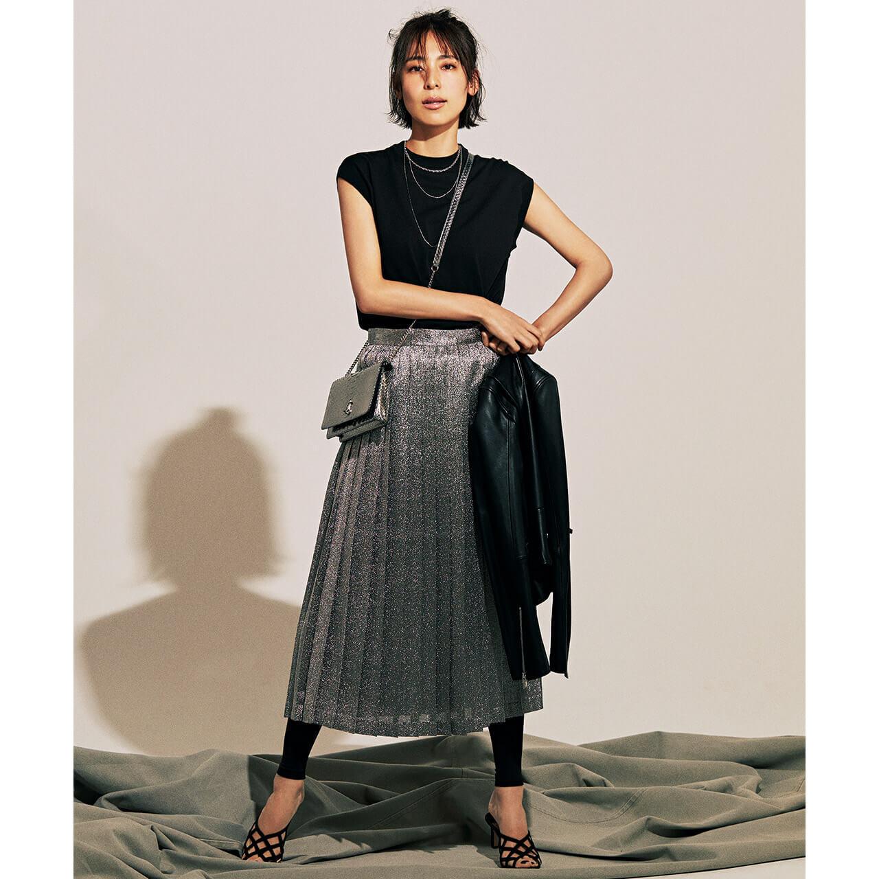 手に持ったジャケット×ニット×シルバーのプリーツスカートコーデを着たモデルの小泉里子さん