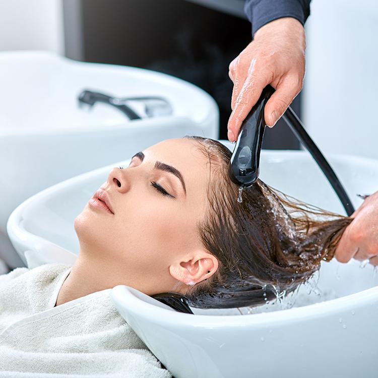 ヘアサロンで髪を洗ってもらうモデル