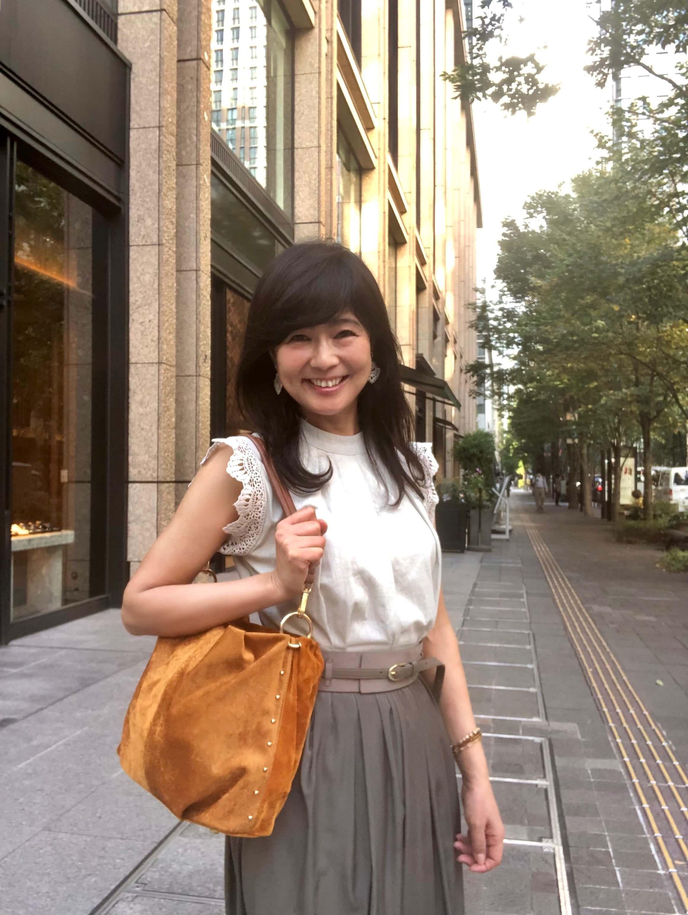 まだ暑いときの秋コーデ。ノースリーブの生成り色トップス、カーキ色のロングスカートに太ベルト。スエード調のキャメル色のバッグ。。