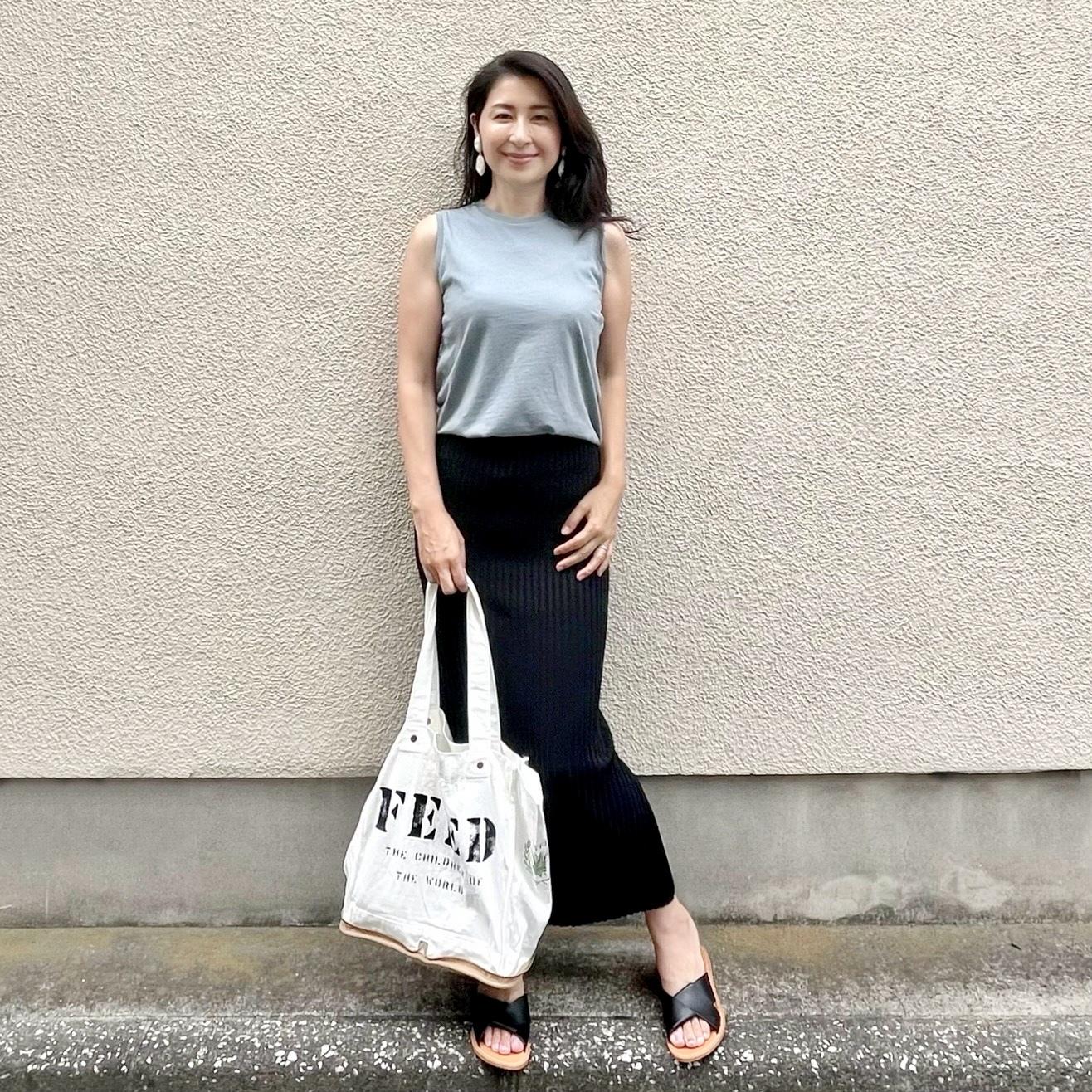 ライトブルーTシャツ、黒ロングタイトスカート、黒サンダル、白エコバッグ