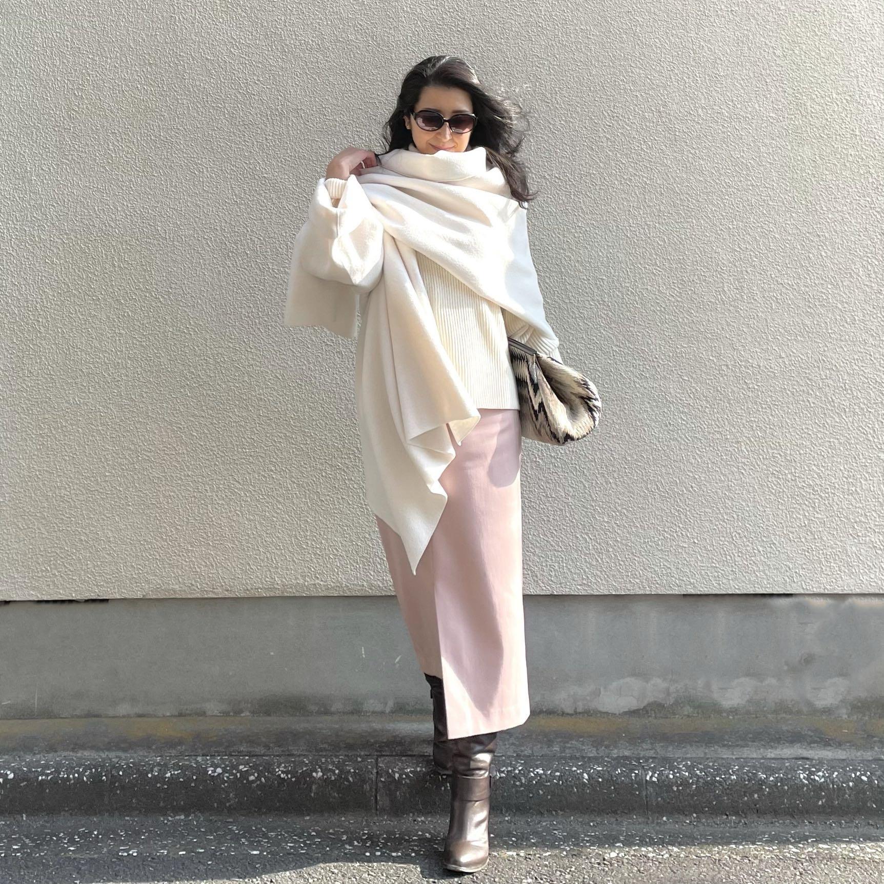 ホワイトの片袖ストール、ホワイトのタートルニット、淡いピンクのタイトスカート、ブラウンのロングブーツ、大きめのクラッチバッグ