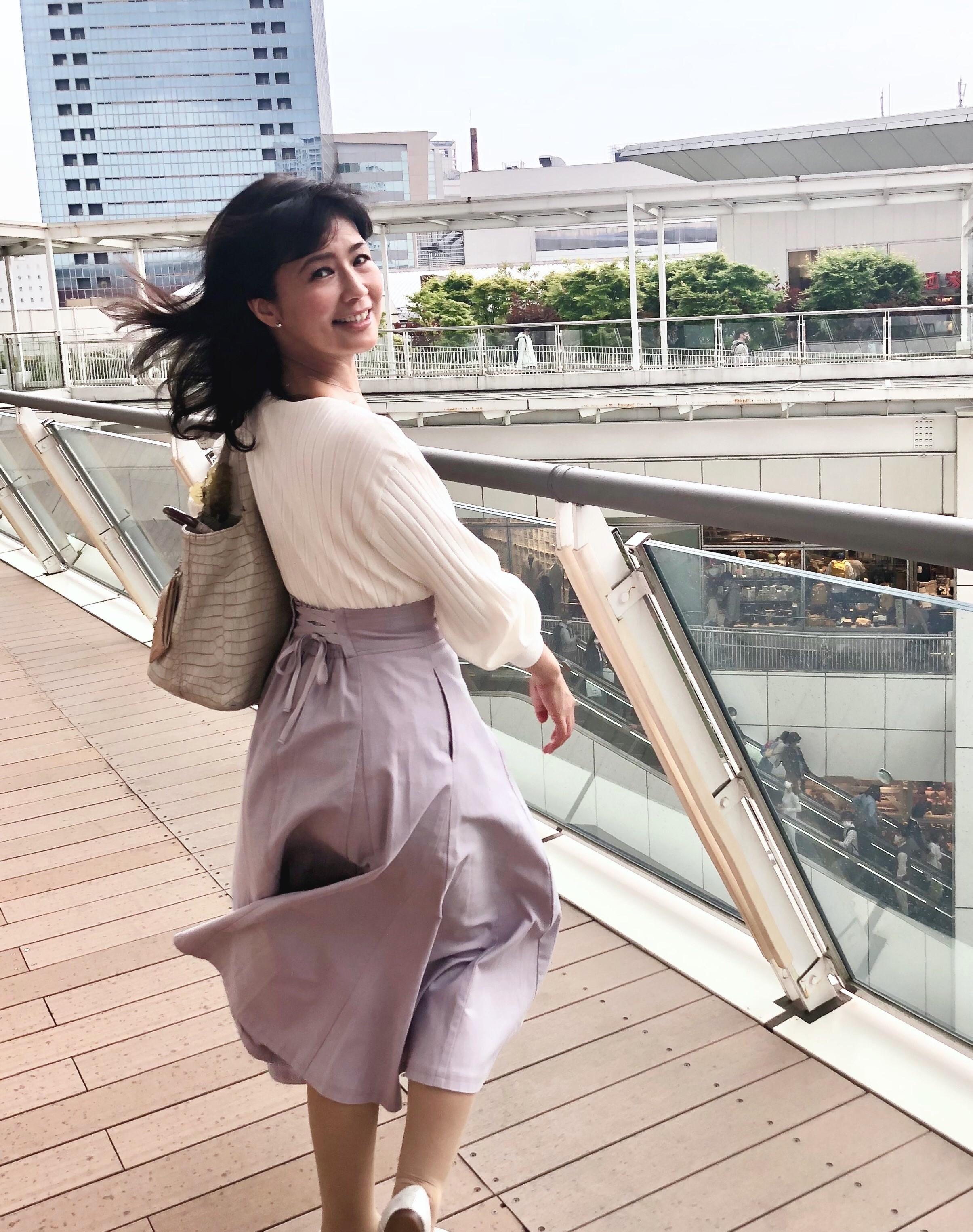 白いトップスに薄紫のロングスカート。振り向いてスカートの後ろのウエストに細いリボンでワンポイント。