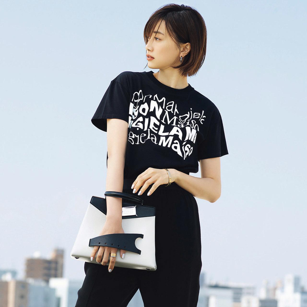黒Tシャツ×メゾン マルジェラのクラッチバッグ