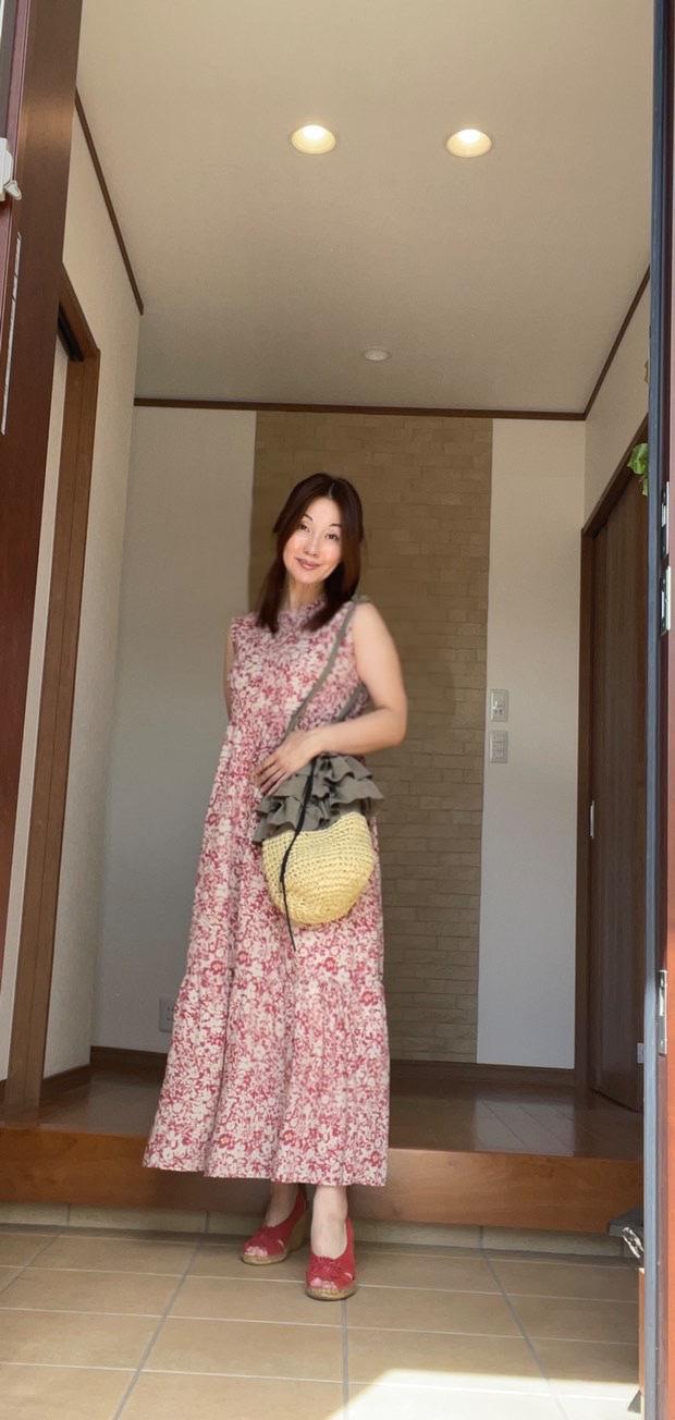 玄関 赤色花柄ワンピースの女性