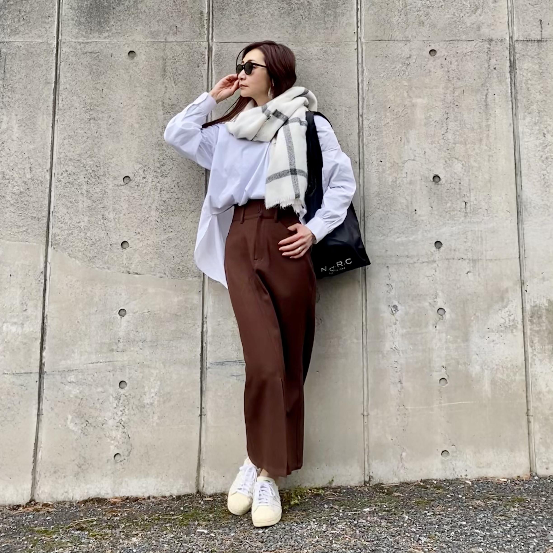 白シャツにロングタイトスカート ストールを巻いて 黒ショッパーバッグを持ってる