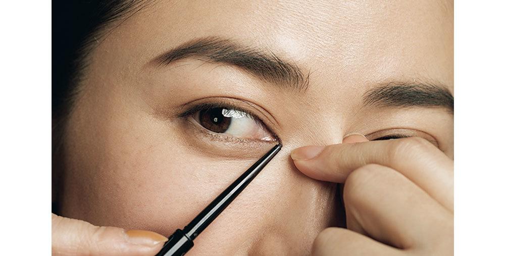 歌舞伎アイラインを引く。鼻のつけ根をつまみ、目頭の内側を見えやすくする。上目頭のまつ毛生えぎわに⑤でラインを引き、目頭の始まりを伸ばす。目じりの生えぎわにも引き、終点を伸ばす。