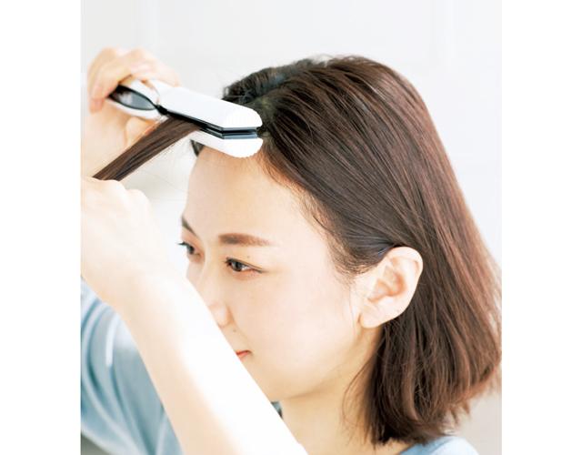前髪の根元をアイロンではさむ