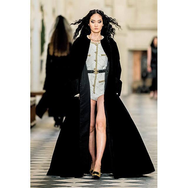 中世をイメージさせ るブラックベルベット のマキシ丈コートのインには、画期的なツイ ードのボディスーツが