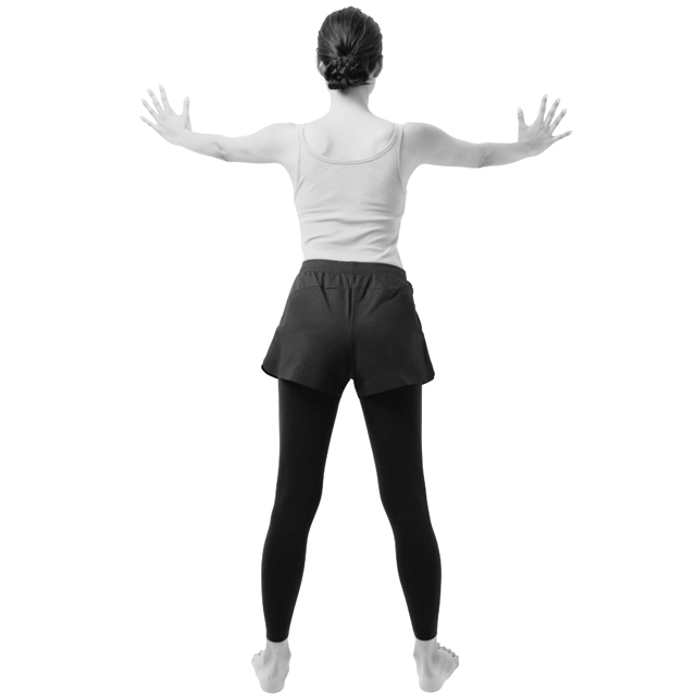 壁に向かって立ち、足を腰幅程度に開く。両腕は大きく広げて、手を壁につける