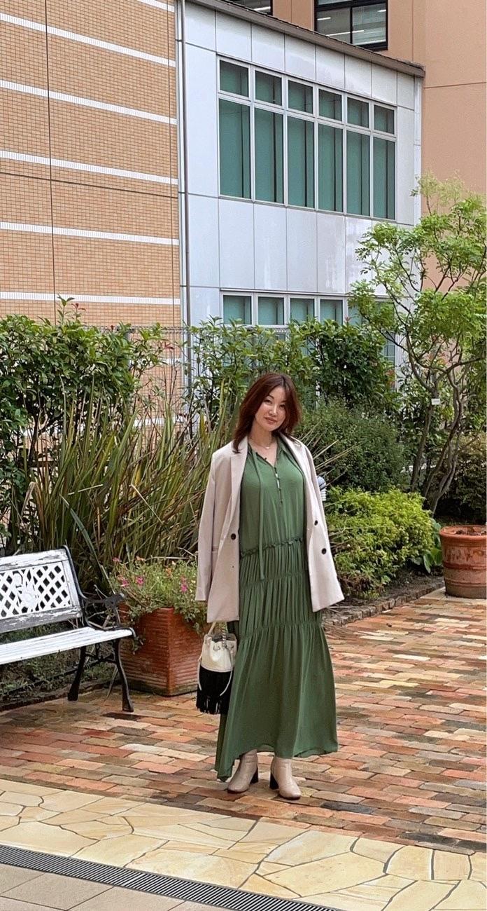 イングリッシュガーデン グリーンのワンピースにベージュのジャケットを肩掛けした女性