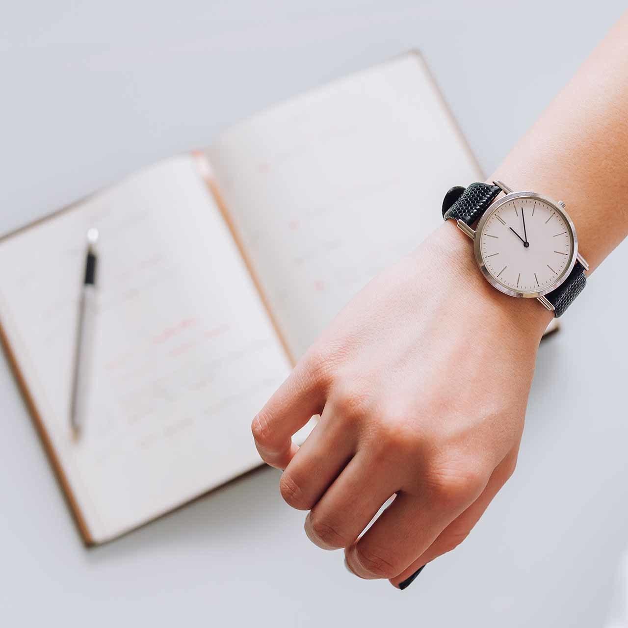 スケジュール管理をする女性の手帳と腕時計