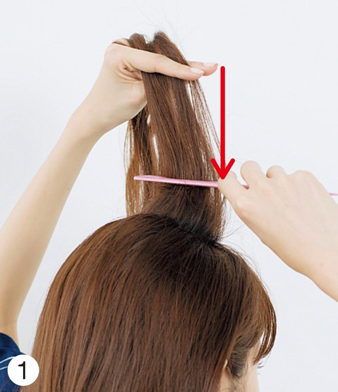 髪の毛全体は、コテでミックス巻きをしておいてね。それから、トップの毛束を取り、写真のようにコームで根元に逆毛を立てる。