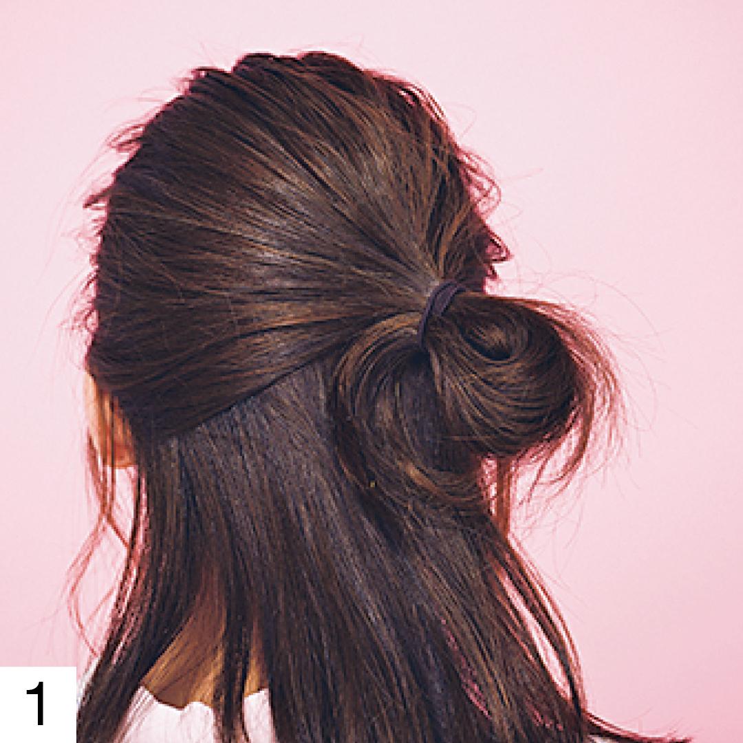 顔回りの髪を少し残したら、ざっくり手ぐしでまとめハーフアップに。結んだ毛先は片側に寄せておだんごに。輪っか部分は多めに引き出し、正面から見えるように。