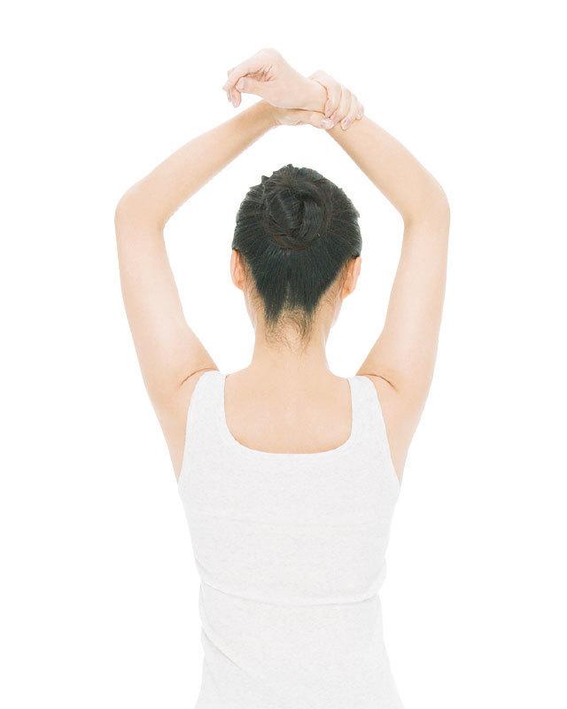 足を軽く開いて立ち、腕を頭上に上げて左手で右手首を持つ。
