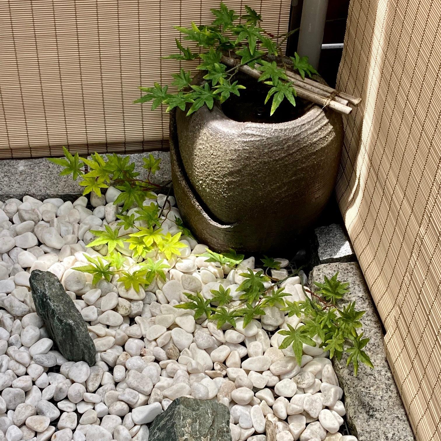 玉砂利を敷いた水琴窟とグリーンのある坪庭