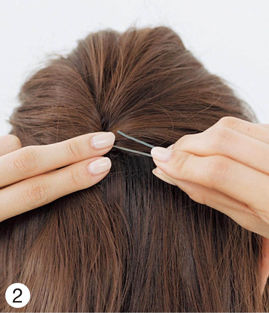 逆毛を立てた毛束をざっくりと集め、頭頂部より少し低いくらいの位置でねじって固定。トップは少しふんわりするように意識を!