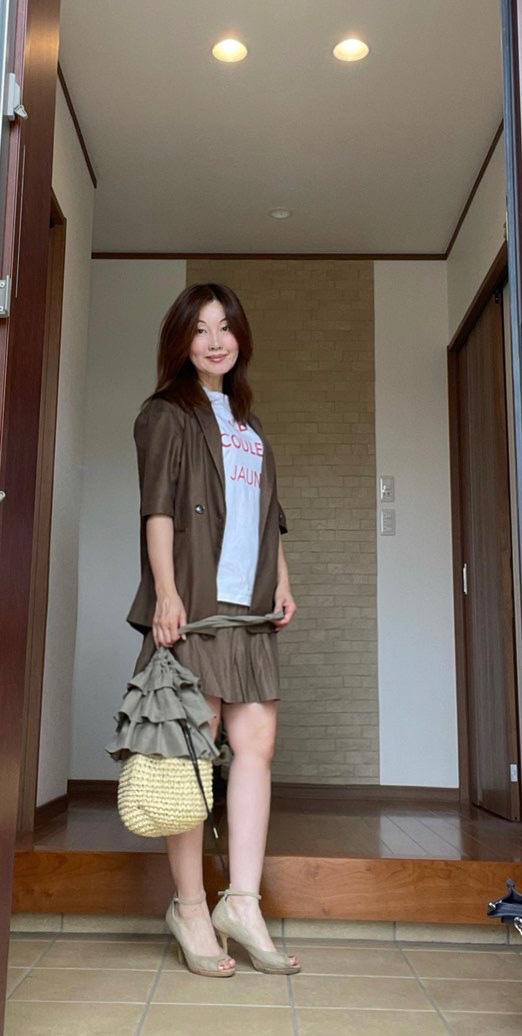 玄関女性 ブラウンの半袖ジャケットにショートパンツ