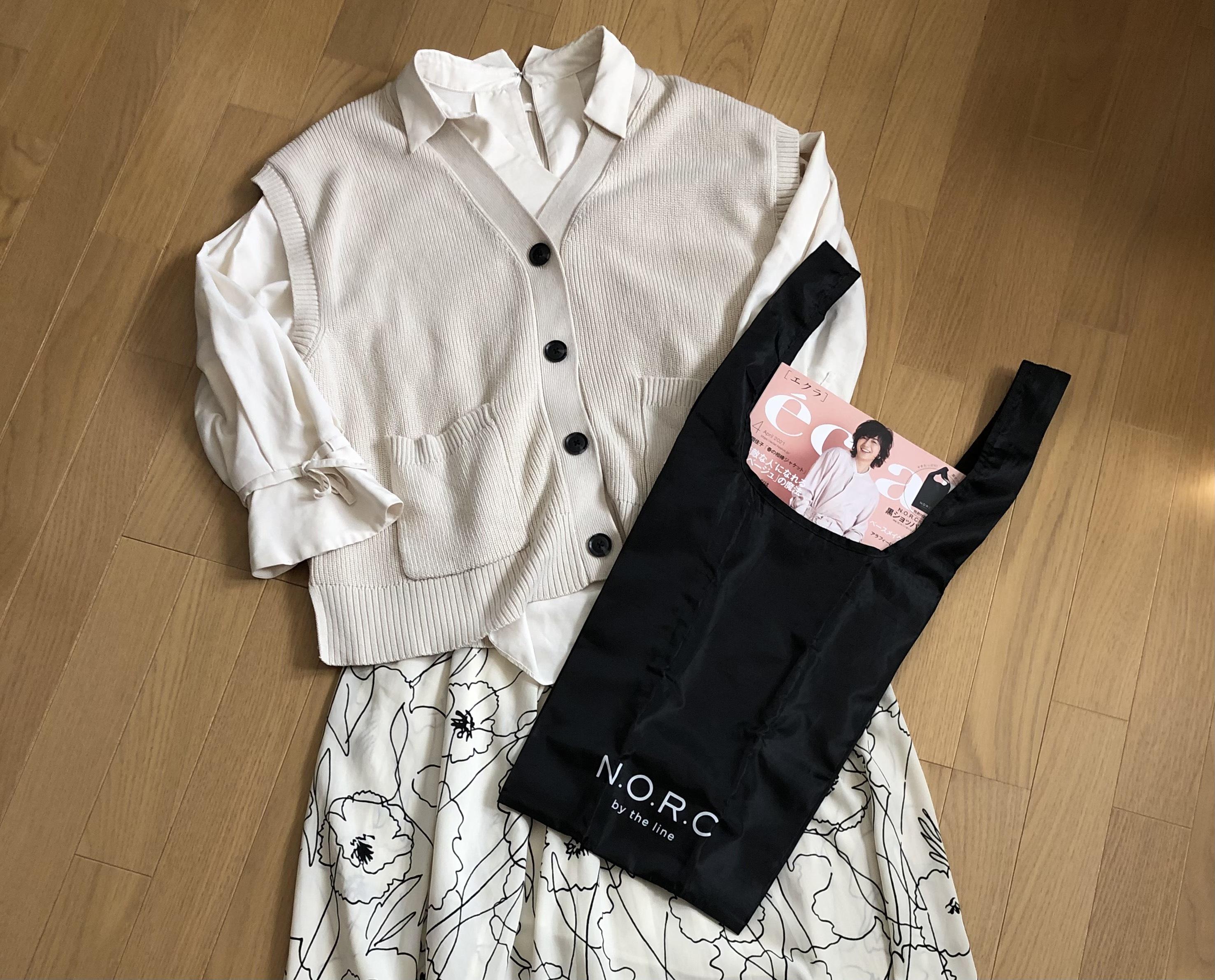 白色ブラウス 白色ニットベスト 白地に黒の模様ロングスカート ショッパーバッグを持って立つ女性 斜め姿