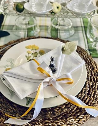 テーブルナプキンに白と黄色のリボンを結んでいます。