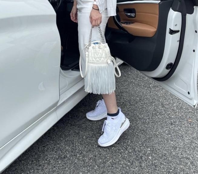 女性足元の写真 白いバッグと白いスニーカー