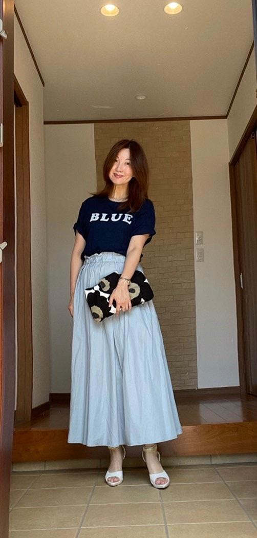 玄関女性 インディゴのTシャツに淡いブルーのマキシスカート