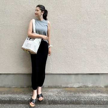 くすみブルーTシャツ、黒のロングニットスカート、黒サンダル、白のエコバッグ