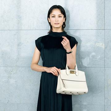 ビジネスウェアに華やかさを!黒ワンピに映える「フェラガモ」の白バッグ