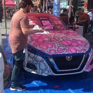 日産の車にアーティストがさくらのペイントを施しているところ。沢山の見物の方々でにぎわっておりました。