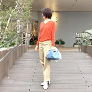 キレのいいオレンジカラーのニットで女っぷり高く